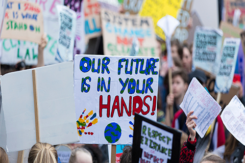 A stock photo of picket signs at a climate change protest.