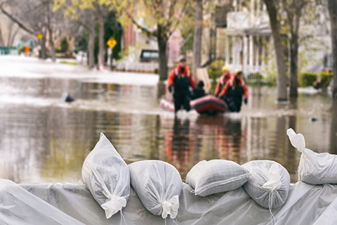 A stock photo of sandbags being used to block a flooded street.