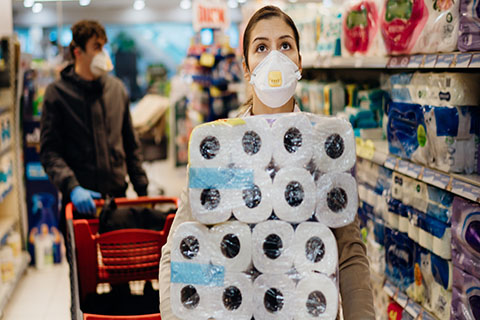 This is a stock photo. A man and a woman in a store shopping for toilet paper and wearing medical masks.